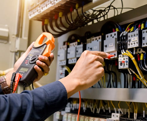 Electrician engineer work tester measuring voltage and current of power electric line in electrical cabinet control.